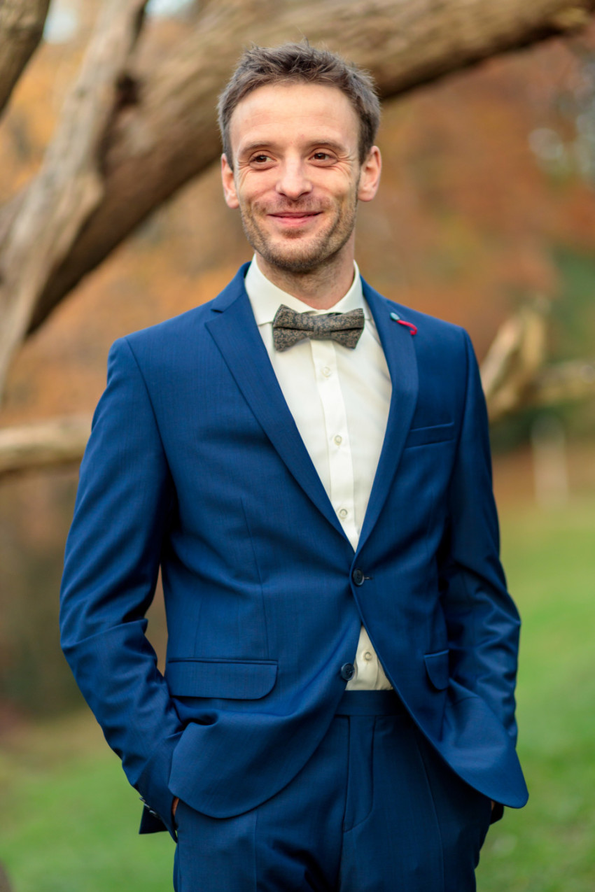 Smiling businessman in a blue suit with a bow tie