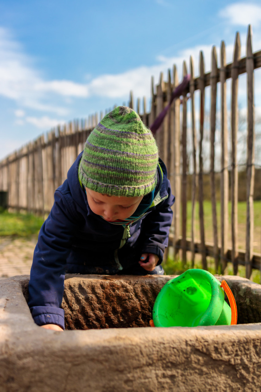 Toddler draws water from a well