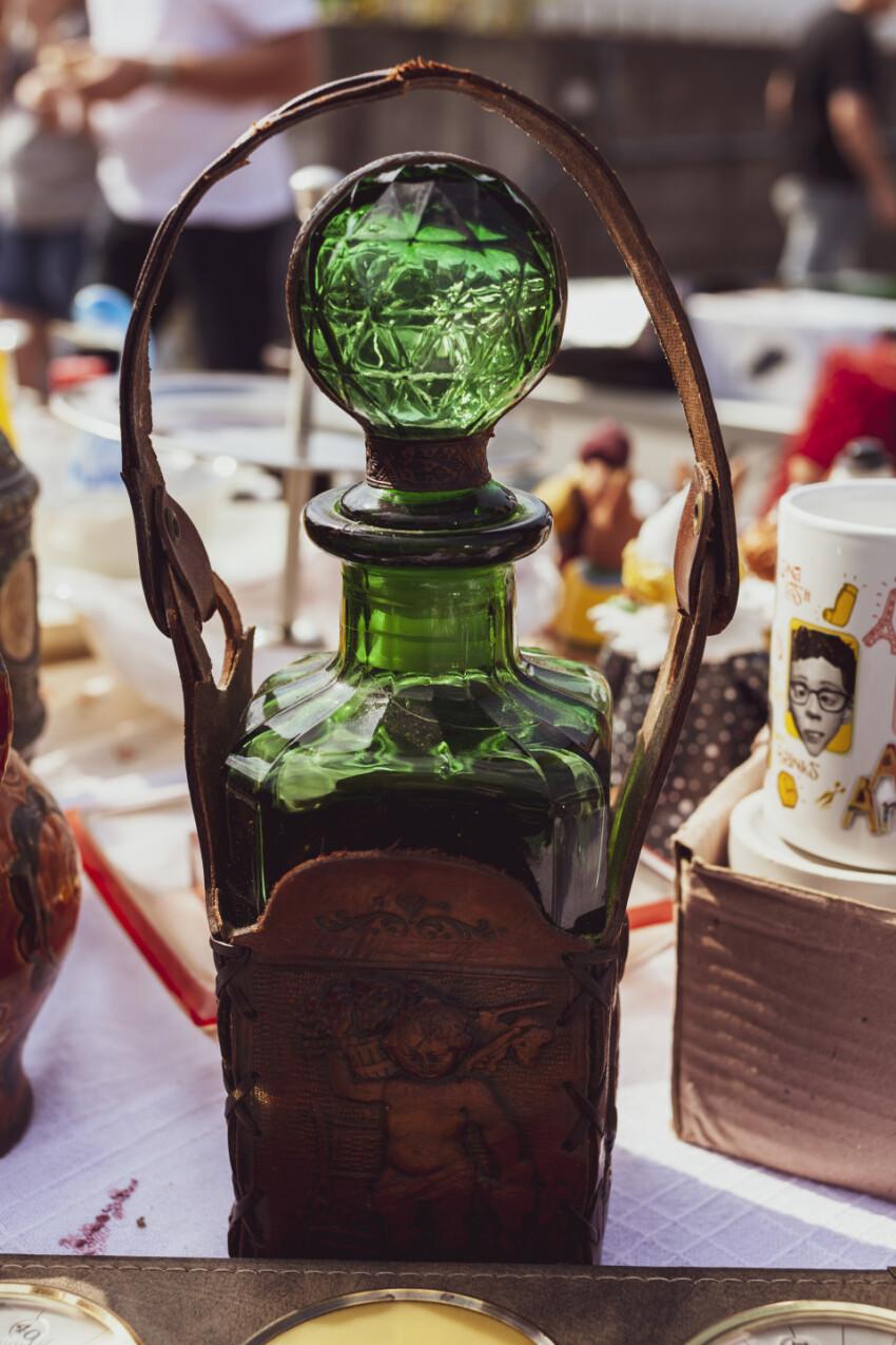 old beautiful green glass bottle on a flea market