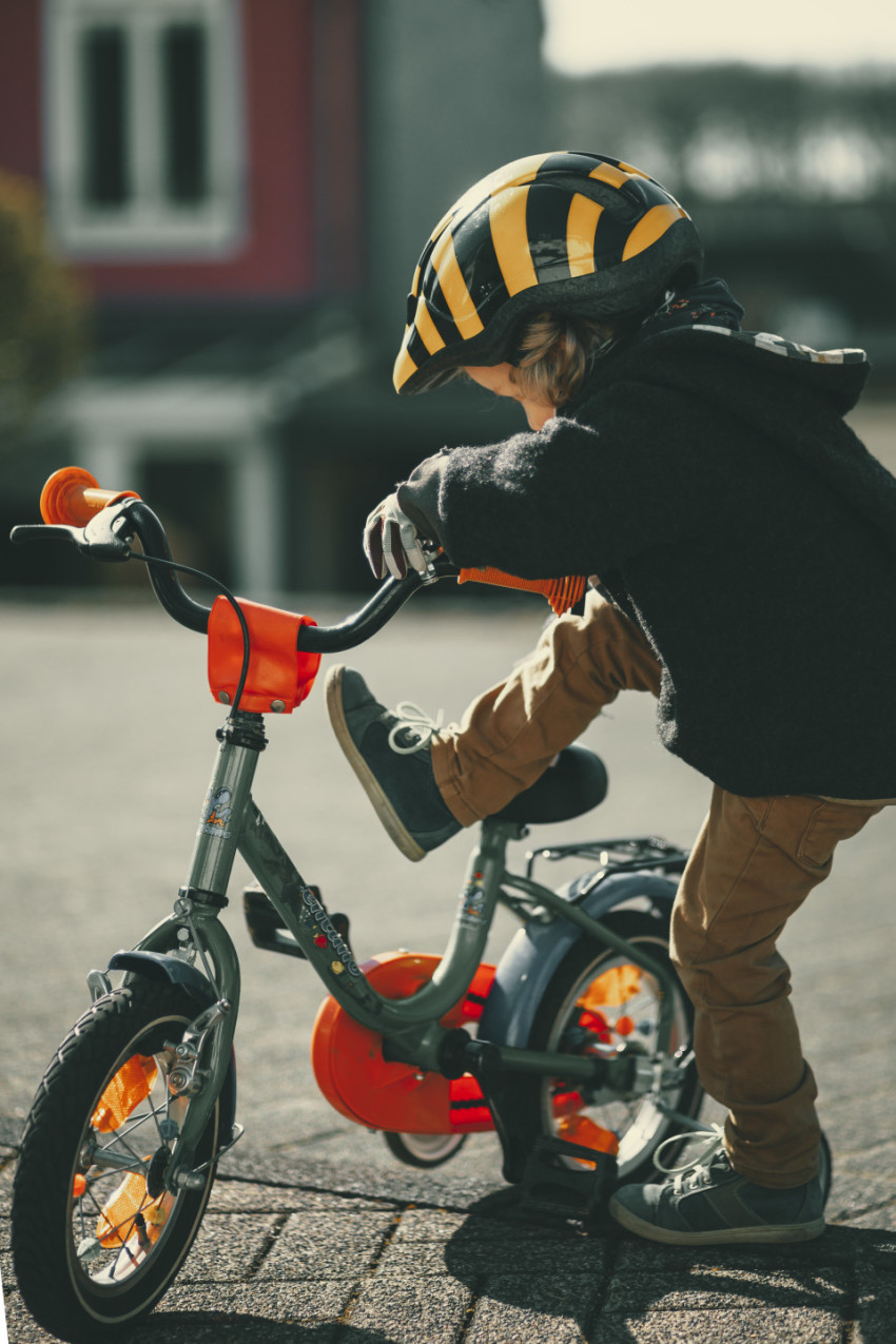 Little boy climbs on a bicycle