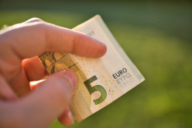 Stock Image: A new 5 Euro bank note in a human hand