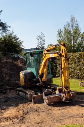 Stock Image: A yellow excavator on a construction site