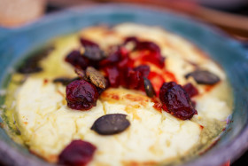 Stock Image: Baked goat cheese with cranberries and pumpkin seeds
