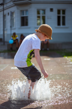 Stock Image: Child plays with the water from a fountain in summer