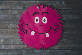 Stock Image: Friendly smiling pink monster on wooden background