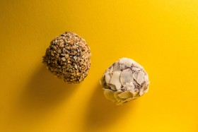 Stock Image: hazelnut and almond pralines on yellow background
