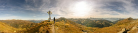 Stock Image: Landscape panorama of the Austrian Alps Hiker stands at the summit cross