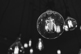 Stock Image: Light bulbs glow in the dark room black and white