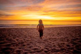 Stock Image: Little blonde girl on the beach at sunset - Portugal Algarve