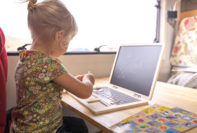 Stock Image: Little girl plays with toy notebook