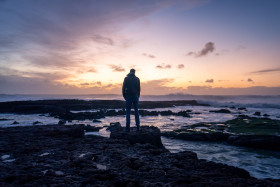 Stock Image: Man looks out to sea towards the sunset