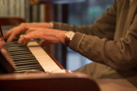 Stock Image: Old hands play the piano