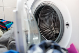 Stock Image: Pile of laundry in front of washing machine