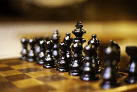 selective focus of wooden chessboard with black chess figures