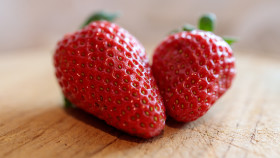 Two strawberries on a wooden board