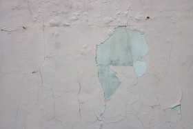 Stock Image: White exterior wall texture with cracked plastering